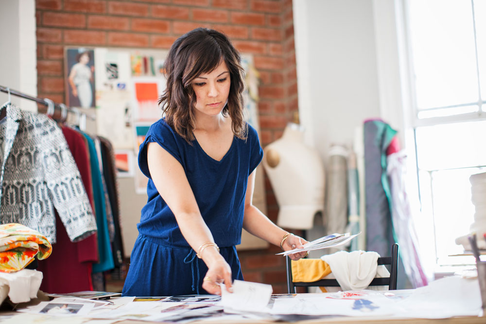 a woman works at her small boutique fashion shop