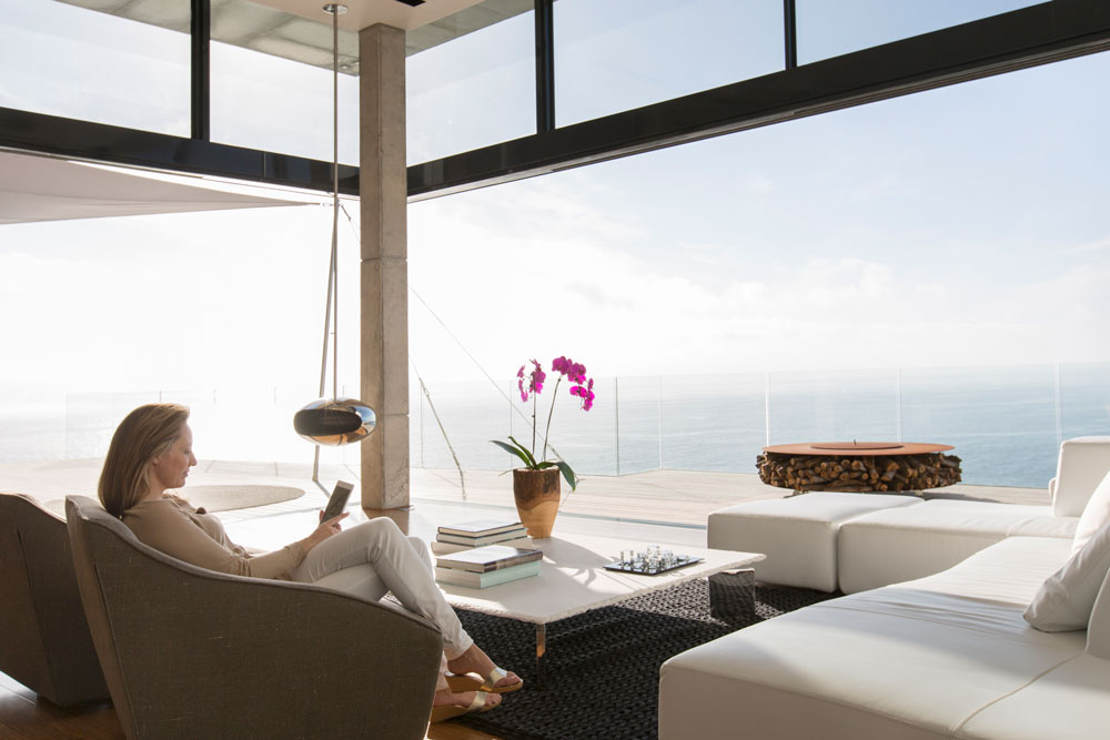 a woman sits reading a book in her house with an ocean view
